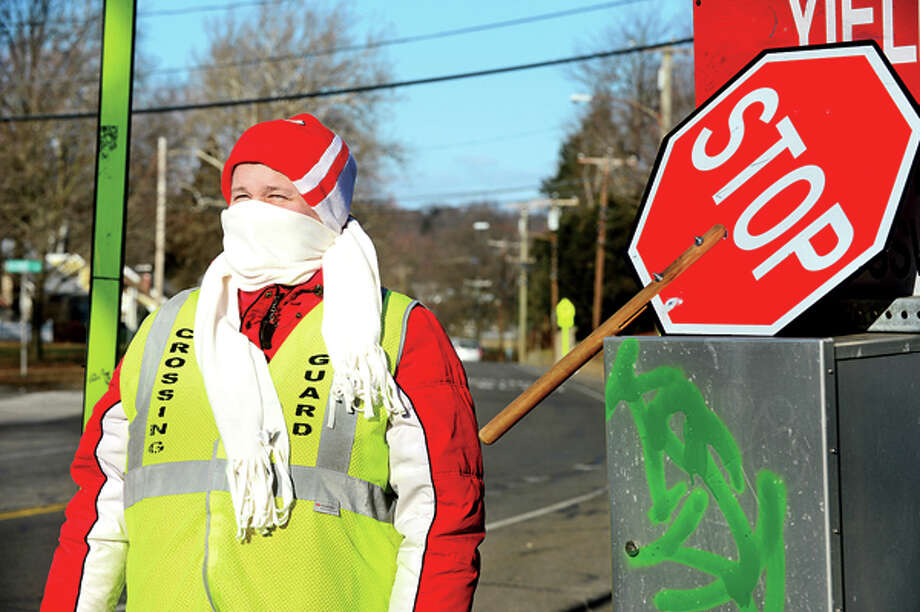 Crossing Guard Donna Eldesouky endures the frigid temperatures to help children cross the streets at Strawberry Hill and King St. Tuesday. Cold temperatures will continue through the week. Hour photo / Erik Trautmann / (C)2012, The Hour Newspapers, all rights reserved