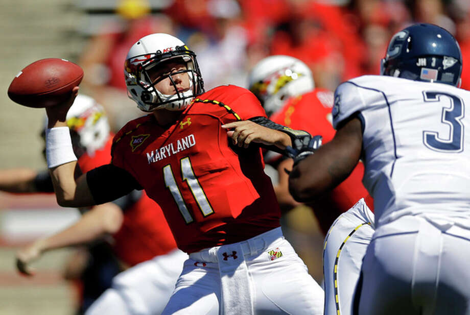 Maryland quarterback Perry Hills (11) throws to a receiver as he is pressured by Connecticut linebacker Sio Moore (3) during the first half of an NCAA college football game in College Park, Md., Saturday, Sept. 15, 2012. (AP Photo/Patrick Semansky) / AP