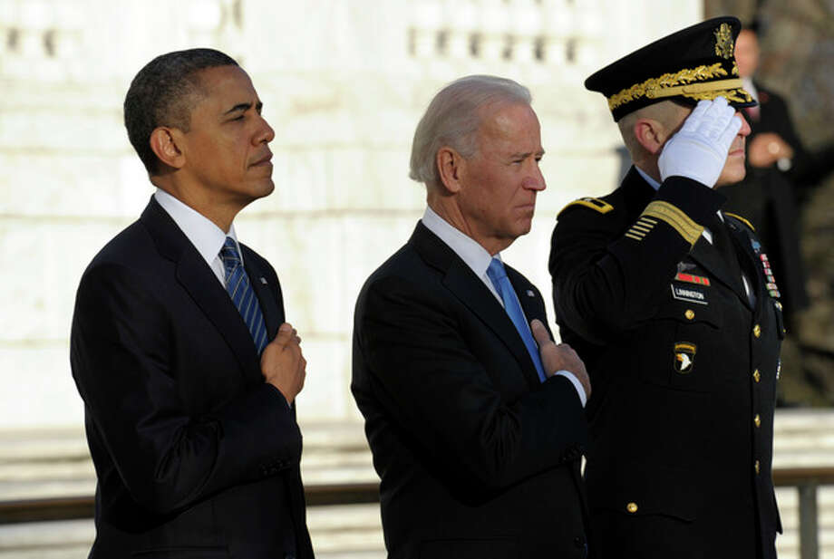 President Barack Obama and Vice President Joe Biden, accompanied by Maj. Gen. Michael S. Linnington, Commander of the U.S. Army Military District of Washington, listen to Taps after placing a wreath at the Tomb of the Unknowns at Arlington National Cemetery in Arlington, Va., Sunday, Jan. 20, 2013. (AP Photo/Susan Walsh) / AP
