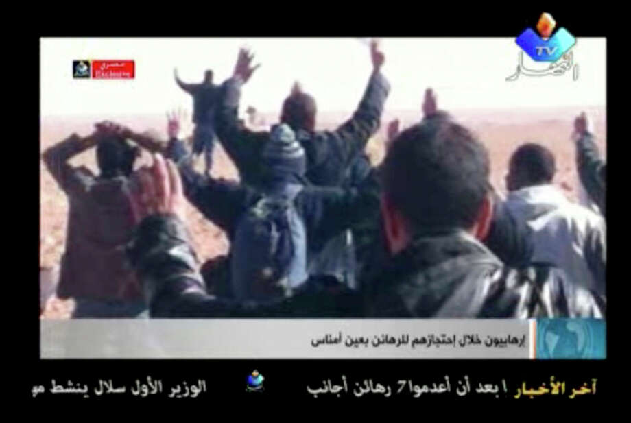 Ap photoIn this image made from video, a group of people believed to be hostages kneel in the sand with their hands in the air at an unknown location in Algeria. Algerian de-mining teams were scouring a gas refinery on Sunday. / ENNAHAR TV