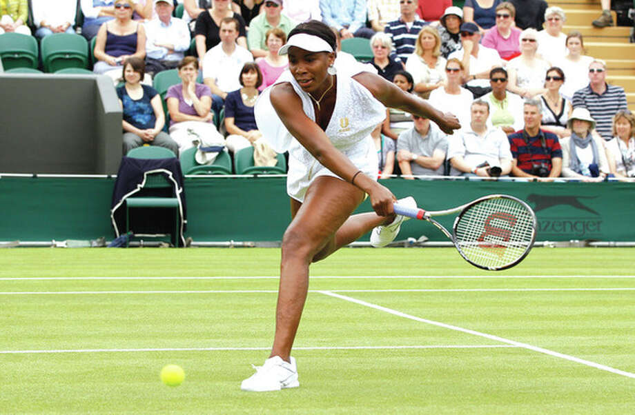AP photo Venus Williams chases down a shot during her match against Akgul Amanmuradova Monday at Wimbledon. Williams overwhelmed Amanmuradova, 6-3, 6-1. / AP
