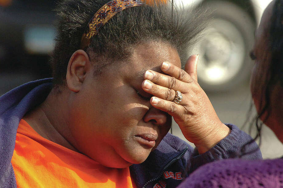 Hour photo / Alex von Kleydorff Margaret Boone fights back tears while family and friends gather on South Main Street at the scene of the death of her husband, William Boone, at his auto repair shop. / 2011 The Hour Newspapers
