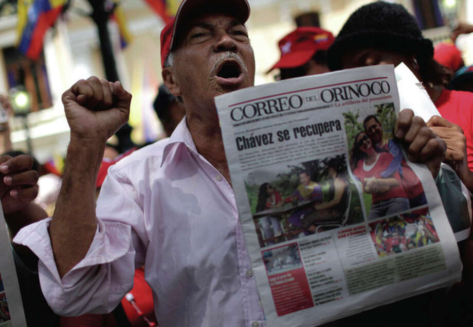 A man chants slogans as he celebrates the return of Venezuela's President Hugo Chavez, in Caracas, Venezuela, Monday July 4, 2011. Chavez returned to Venezuela from Cuba on Monday morning, stepping off a plane hours before dawn and saying he is feeling better as he recovers from surgery that removed a cancerous tumor. The man is holding a a newspaper that shows pictures of Chavez and his daughters during his recuperation in Havana, Cuba. (AP Photo/Ariana Cubillos) / AP