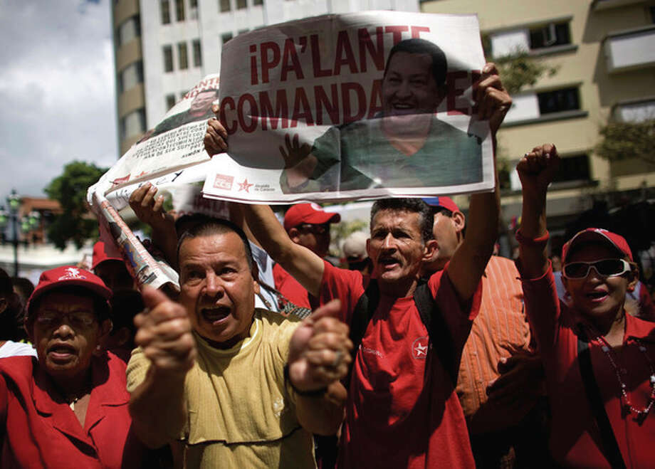 People celebrate the return of Venezuela's President Hugo Chavez, holding posters bearing his image that read in Spanish; / AP