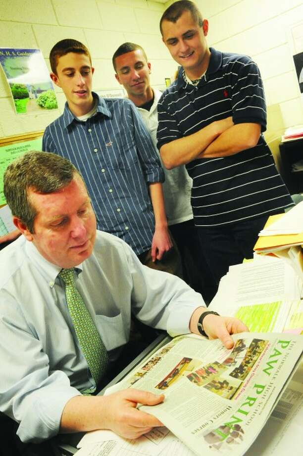 Norwalk High School 12th graders, Brendon Prescott, Matt Cranston and James Cooksey get feedback from guidence councilor John O''Donnell at the school Monday on the latest edition of the Paw Print thier school newspaper. hour photo/matthew vinci