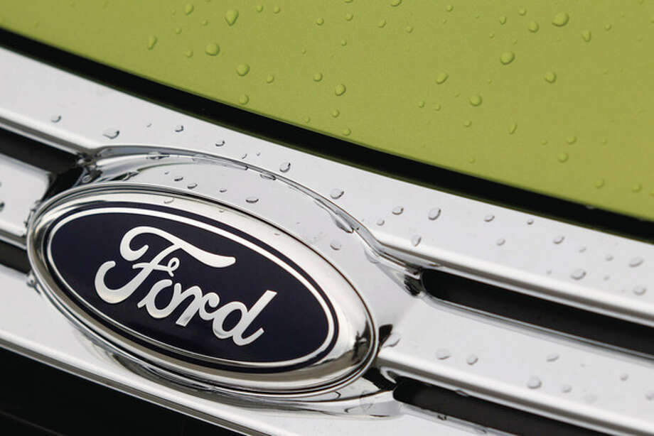 This Aug. 31, 2011 photo, shows raindrops on the grill of a Lime Squeeze Metallic 2012 Ford Fiesta SE at the Maroone Ford of Miami dealership. Ford Motor Co. and the United Auto Workers have come to terms on a new four-year contract Tuesday, Oct. 4, 2011, that trades annual pay raises for profit sharing and a signing bonus and promises thousands of new jobs building cars and trucks. (AP Photo/Wilfredo Lee) / AP