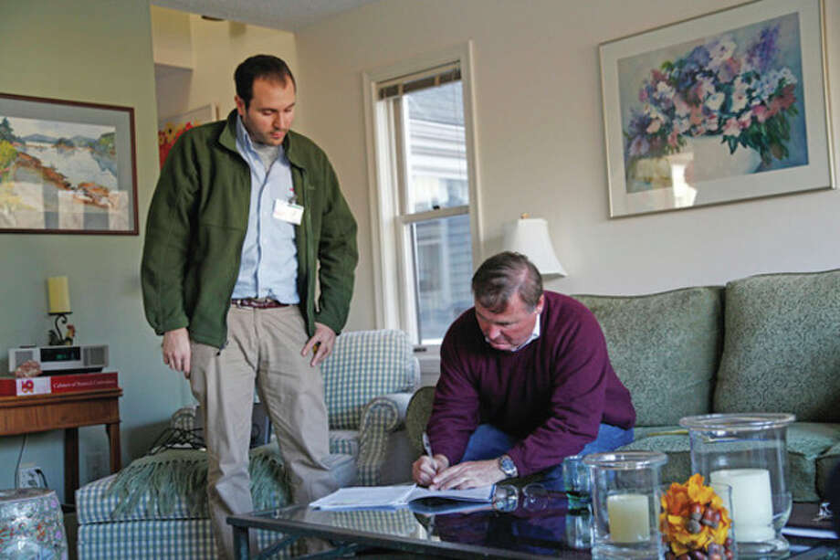 Jason Mackowski, a representative from Wesson Energy, explains the process of an energy audit to Wilton Selectman Hal Clark in his home Friday afternoon. Hour Photo / Danielle
