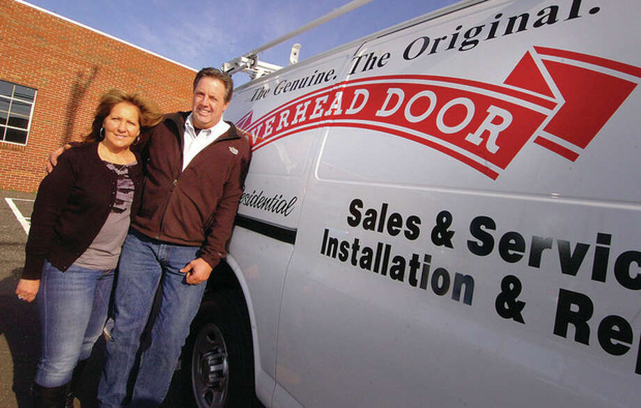 Hour Photo/ Alex von Kleydorff Cathy and Mark Hunihan, owners of Overhead Door Company of Fairfield County, stand in front of their new location on Broad Street in Norwalk. Below, operations manager, Patrick Kelly, in the showroom. / 2011 The Hour Newspapers