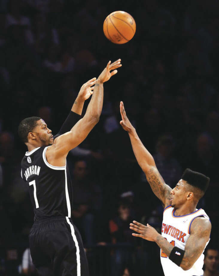 AP photoBrooklyn Nets guard Joe Johnson, left, shoots over New York Knicks guard Iman Shumpert during the first half of Monday's game. Johnson hit the go-ahead jumper with 22 seconds to go and the Nets won, 88-85.