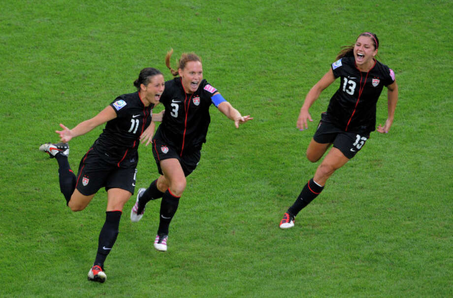 United States' Alex Krieger, left, celebrates with teammates Christie Rampone and Alex Morgan, right, after scoring the decisive penalty shot during the quarterfinal match between Brazil and the United States at the WomenÕs Soccer World Cup in Dresden, Germany, Sunday, July 10, 2011. (AP Photo/Jens Meyer) / AP