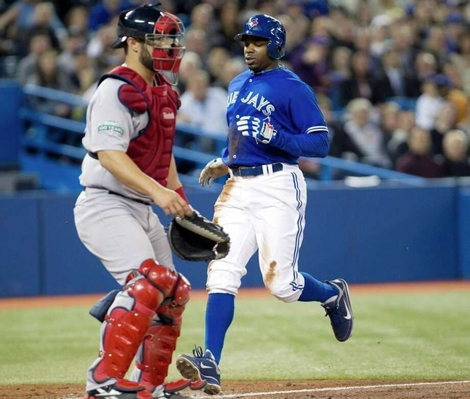 Toronto Blue Jays' Rajai Davis crosses the plate to score behind Boston Red Sox catcher Kelly Shoppach during third inning of a baseball game in Toronto on Wednesday, April 11, 2012. (AP Photo/The Canadian Press, Frank Gunn) / CP