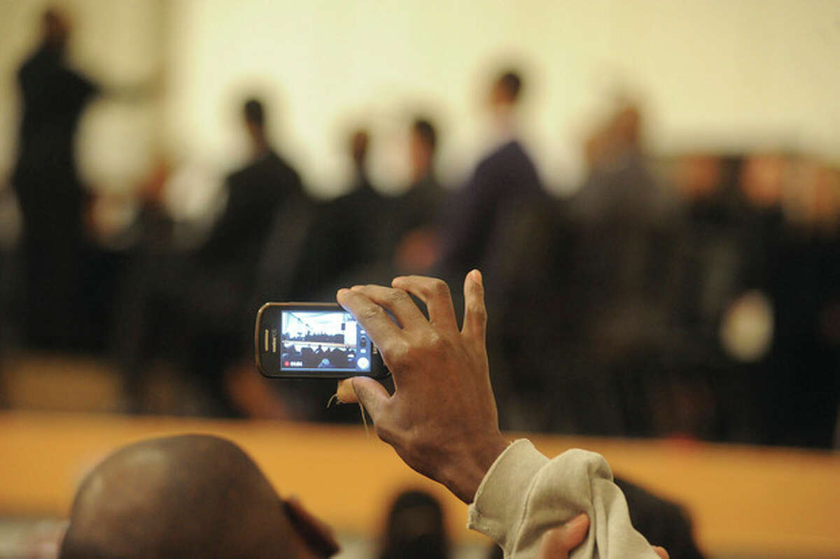 Hour photo / Matthew Vinci A man videotapes the celebration Monday night at the memorial service honoring the Rev. Martin Luther King Jr. at Norwalk City Hall.