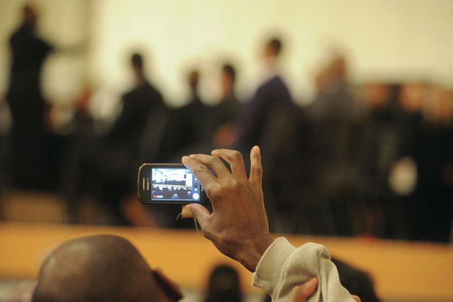 Hour photo / Matthew VinciA man videotapes the celebration Monday night at the memorial service honoring the Rev. Martin Luther King Jr. at Norwalk City Hall.