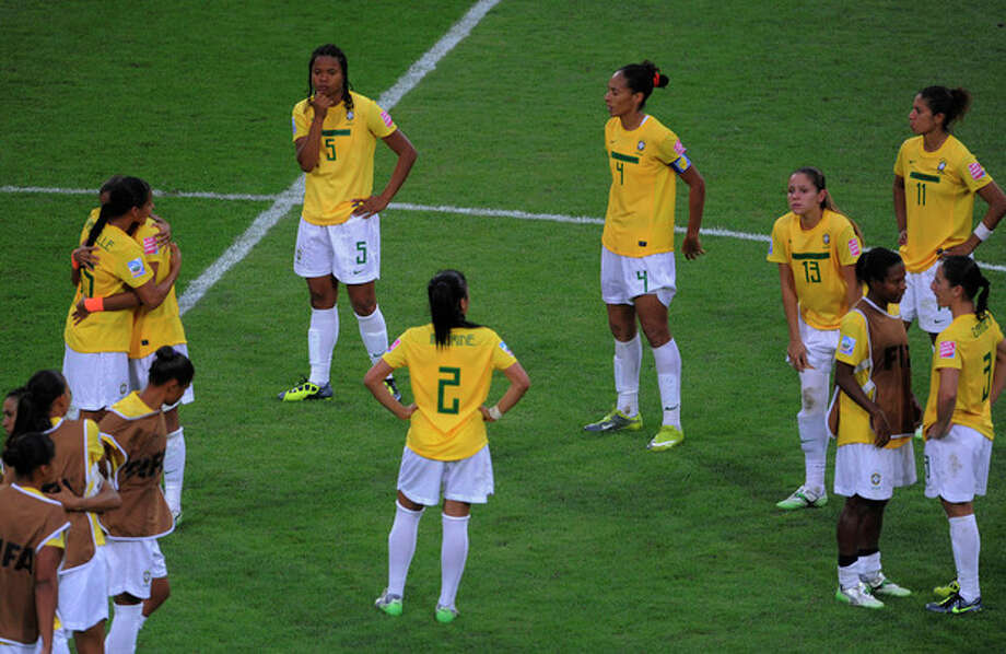 Brazil players stand on the pitch after losing in a penalty shootout the quarterfinal match between Brazil and the United States at the Women's Soccer World Cup in Dresden, Germany, Sunday, July 10, 2011. (AP Photo/Jens Meyer) / AP2011