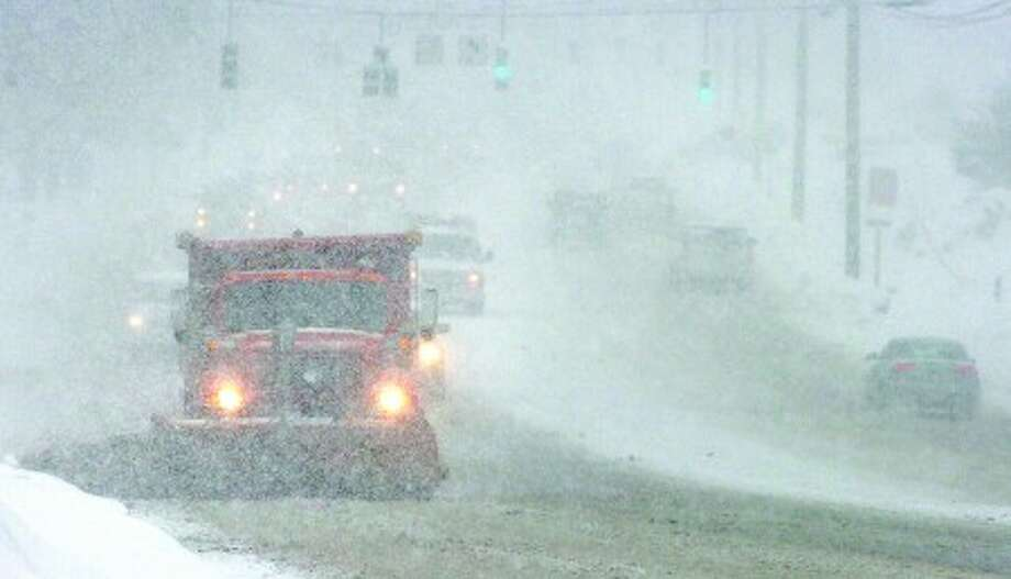 Photo/Alex von Kleydorff. A state snowplow heads north on Rt 7 Wilton past Town Hall in blinding snow at the height of the morning snowstorm on Wednesday.