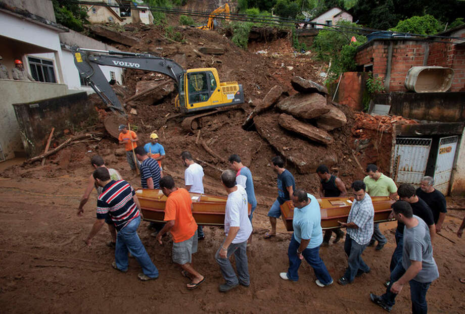 Relatives carry the coffins of a family killed by a mudslide to the cemetery in Jamapara, Rio de Janeiro state, Brazil, Tuesday Jan. 10, 2012. Sergio Carvalho, his wife Solange and their son Tiago were buried by a mudslide that killed at least eight people and left 20 people missing. According to civil defense officials, at least 23 people have died this year due to mudslides triggered by heavy rains. (AP Photo/Victor R. Caivano) / AP