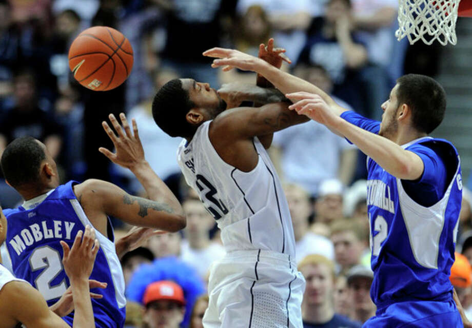 Connecticut's Roscoe Smith, center, is fouled by Seton Hall's during Aaron Geramipoor, right, during the second half of Connecticut's 69-46 victory in an NCAA college basketball game in Hartford, Conn., on Saturday, Feb. 4, 2012. (AP Photo/Fred Beckham) / FR153656 AP
