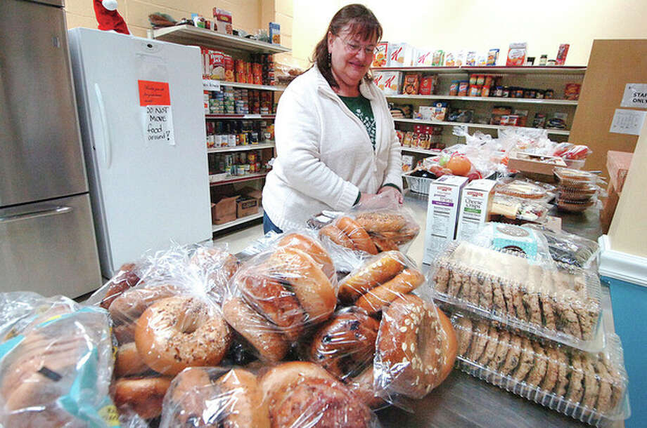 Hour photo / Alex von Kleydorff Christian Community Action Center Executive Director Christi Pope sorts bags of bagels among donated items in the food bank in the center's new building Tuesday. / 2012 The Hour Newspapers