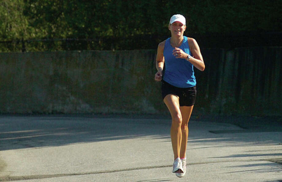 Liz Herbert of Darien finishes first among the women during the Westport Road Runners 8th race of 10 in the summer series at Burying Hill Beach Saturday morning. / (C)2011, The Hour Newspapers, all rights reserved