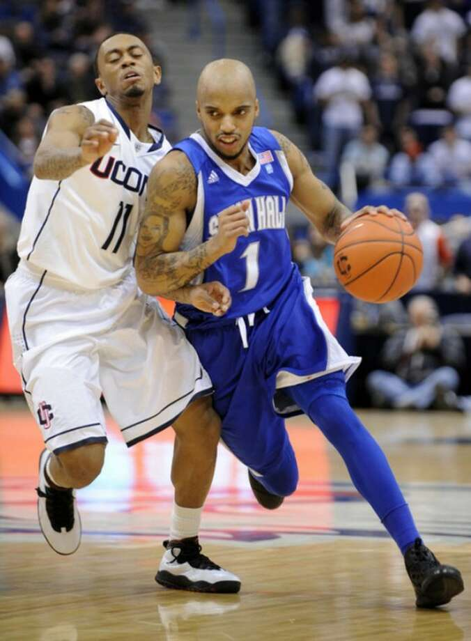 Seton Hall's Jordan Theodore, right, drives past Connecticut's Ryan Boatright during the first half of an NCAA college basketball game in Hartford, Conn., on Saturday, Feb. 4, 2012. (AP Photo/Fred Beckham)