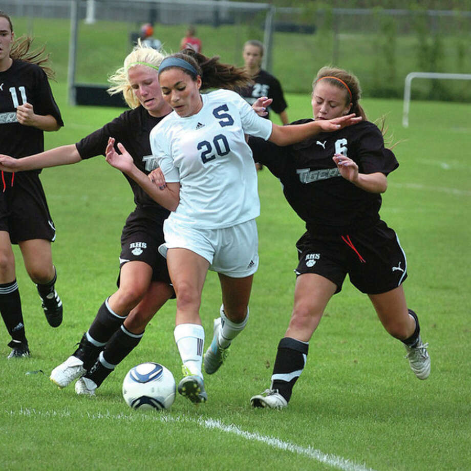 Hour photo/Alex von Kleydorff Abbie Lake of Staples, center, fights to control the ball against Ridgefield's Amy Reunert, left, and Maggie Brassinga during Wednesday's match in Westport. Lake had two goals in the Wreckers' 8-2 victory. / 2011 The Hour Newspapers/ Alex von Kleydorff