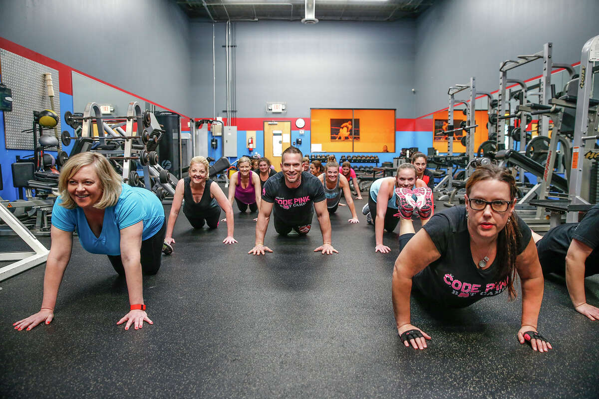 Paul Moran of Code Pink Boot Camp leads his boot camp class for women through a push-up routine at Gracie Barra Gym, 21734 Provincial Blvd. in Katy.