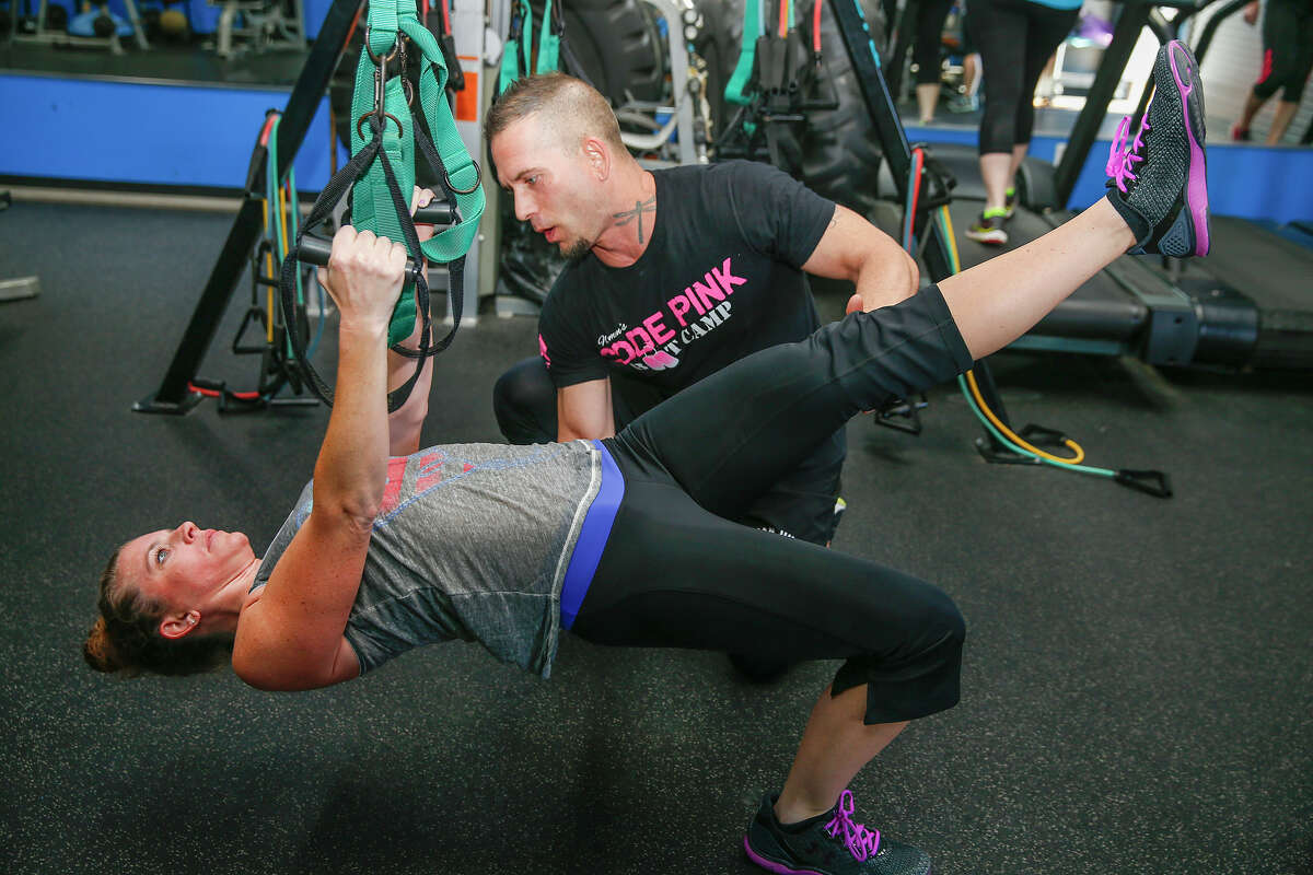 Code Pink Boot Camp operator Paul Moran guides Suzanne Mosley through core exercises.