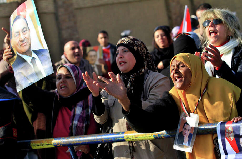 Egyptian women carrying photos of ousted Egyptian President Mubarak, demonstrate outside a courtroom in Cairo, Egypt, Tuesday, Jan. 17, 2012. Hosni Mubarak and his two sons, wealthy businessman Alaa and his one-time heir apparent Gamal face corruption charges and all three were in court Tuesday. (AP Photo/Khalil Hamra) / AP