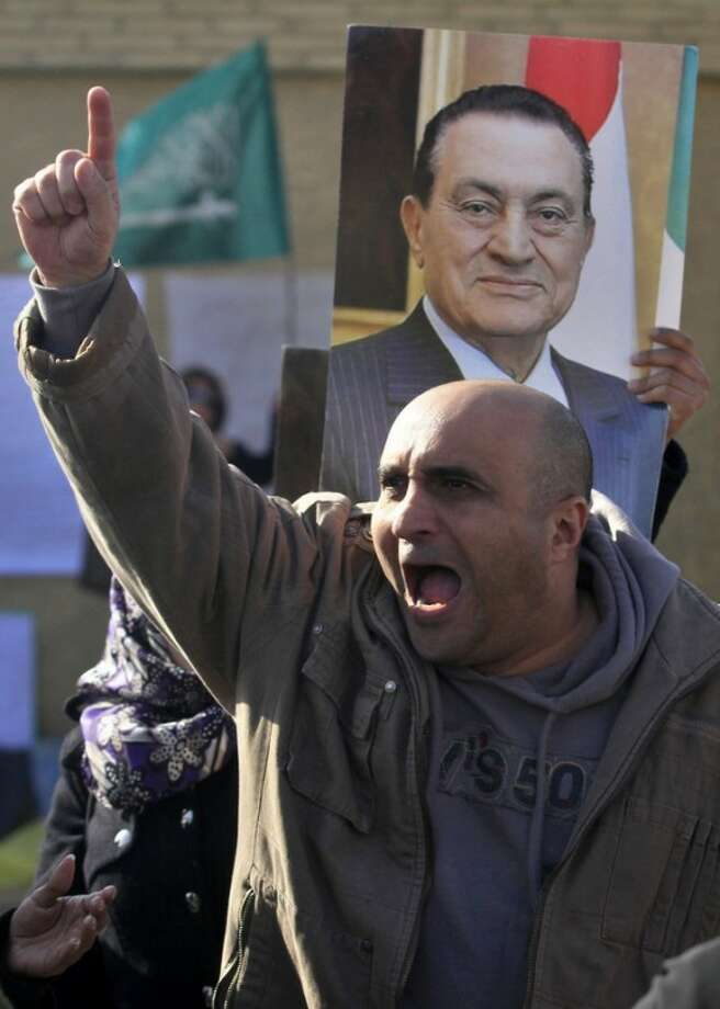 An Egyptian man chants slogans in front of a courtroom in Cairo, outside a courtroom in Cairo, Egypt, Tuesday, Jan. 17, 2012. Hosni Mubarak, seen in poster behind, and his two sons, wealthy businessman Alaa and his one-time heir apparent Gamal face corruption charges and all three were in court Tuesday. (AP Photo/Khalil Hamra)