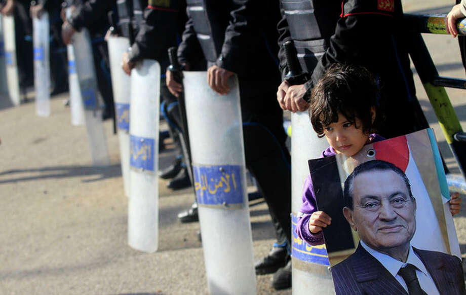 An Egyptian girl carrying a photo of ousted Egyptian President Mubarak, stands next to riot police outside a courtroom in Cairo, Egypt, Tuesday, Jan. 17, 2012. Hosni Mubarak and his two sons, wealthy businessman Alaa and his one-time heir apparent Gamal face corruption charges in the same case and all three were in court Tuesday, prompting increased security outside the court. (AP Photo/Khalil Hamra) / AP