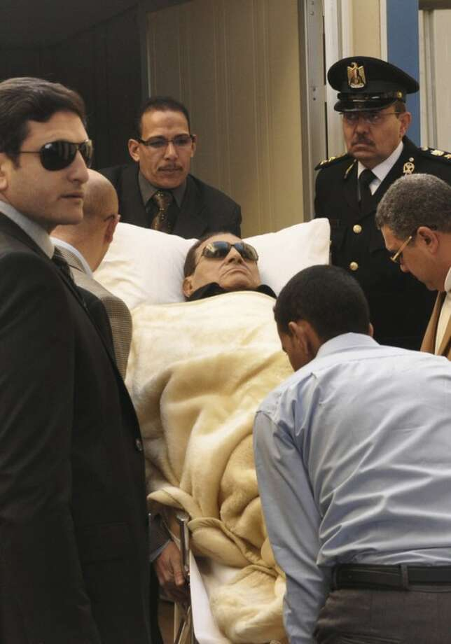 Former Egyptian president Hosni Mubarak is wheeled into a court house in Cairo, Egypt, Tuesday, Jan. 17, 2012. Mubarak faces charges of complicity in the killing of hundreds of protesters during an 18-day uprising that toppled his regime nearly a year ago. If convicted, Mubarak, 83, could face a death penalty. (AP Photo/Mohammed al-Law)