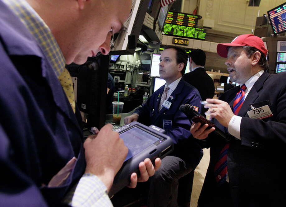 Trader Edward Schreier, right, works with specialist John Alatzas, center, on the floor of the New York Stock Exchange Friday, Feb. 3, 2012. U.S. stocks are opening sharply higher after the unemployment rate dropped to the lowest in two years. (AP Photo/Richard Drew) / AP