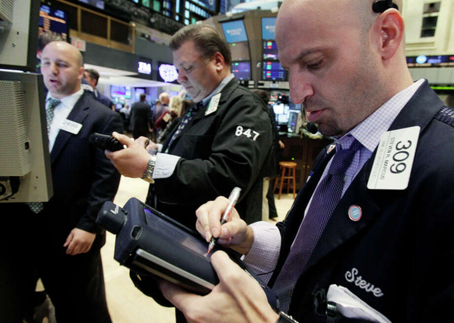 In this Dec. 20, 2011 photo, Steven Marcus, right, works with fellow traders on the floor of the New York Stock Exchange. European stock markets extended gains Wednesday, Dec. 21, on a wave of pre-holiday optimism after the European Central Bank loaned a record amount to the continent's banks in an effort to bolster Europe's stressed financial system. (AP Photo/Richard Drew) / AP