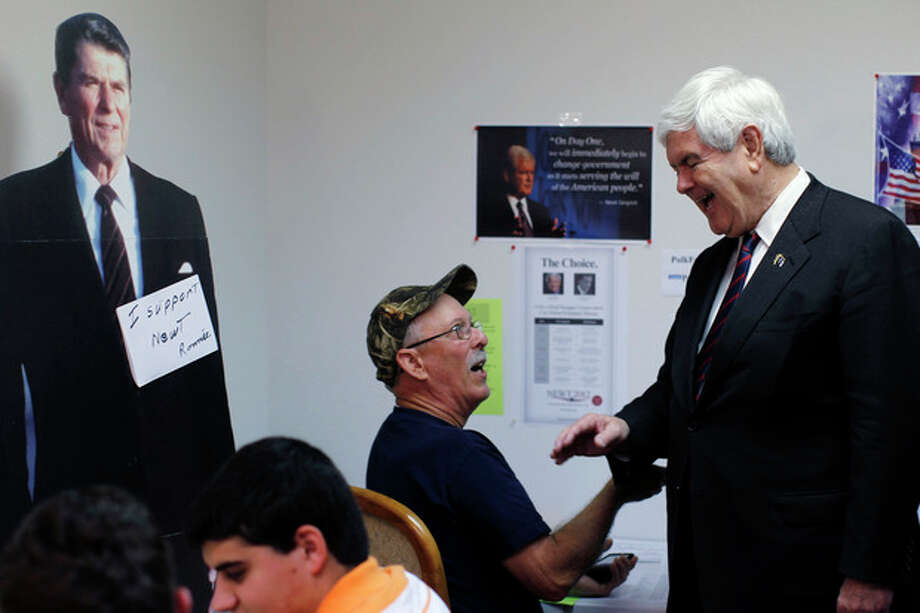 Republican presidential candidate, former House Speaker Newt Gingrich meets with campaign workers in view of a cutout of former President Ronald Reagan during a visit to the Polk County campaign office, Tuesday, Jan. 31, 2012, in Lakeland, Fla. (AP Photo/Matt Rourke) / AP