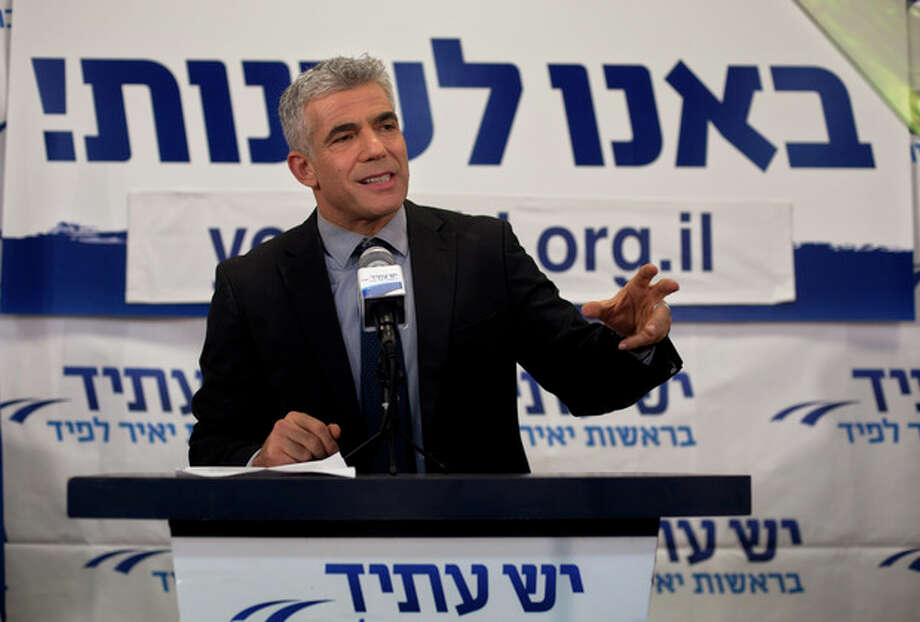 "Yair Lapid gestures as he delivers a speech at his ""Yesh Atid"" party in Tel-Aviv, early Wednesday, Jan. 23, 2013. The party, formed just over a year ago, out did forecasts by far and are predicted to capture as many as 19 seats, becoming parliament's second-largest party, after Netanyahu's Likud-Beiteinu bloc, which won 31, according to the exit polls. (AP Photo/Sebastian Scheiner) / AP"