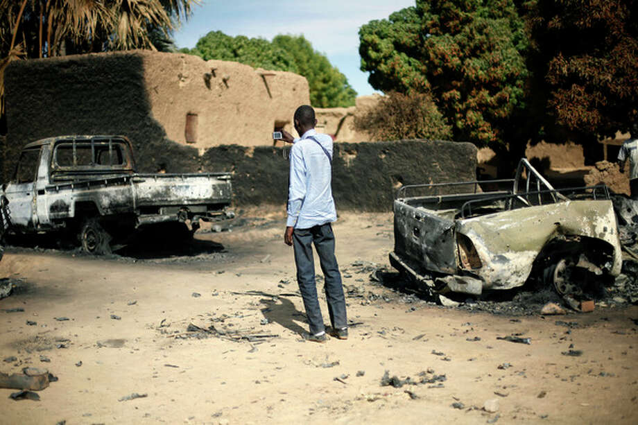 An unidentified man takes a picture of the charred remains of trucks used by radical Islamists on the outskirt of Diabaly, Mali, some 460kms (320 miles) North of the capital Bamako Monday Jan. 21, 2013. French and Malian troops took control Monday of the town of Diabaly, patrolling the streets in armored personnel carriers and inspecting the charred remains of a pickup truck with a mounted machine gun left behind by the fleeing militants. (AP Photo/Jerome Delay) / AP