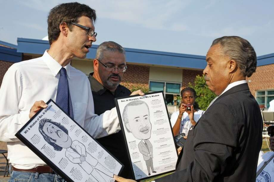 Artist Robert Carley presents Al Sharpton with charactertures he made at a local NAACP rally in support of Tonya McDowell held at Brookside School in Norwalk Tuesday evening. Hour Photo / Danielle Robinson