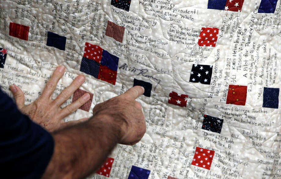 Republican presidential candidate, former Massachusetts Gov. Mitt Romney, points to his signature on a quilt he signed earlier, with messages from supporters, Tuesday, Jan. 31, 2012, at his campaign office in Tampa, Fla. (AP Photo/Charles Dharapak) / AP