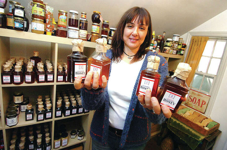 Hour photos / Alex von Kleydorff Red Bee Honey founder/owner Marina Marchese holds some of her handcrafted Wildflower, Goldenrod, Blueberry, and Buckwheat honey. / © 2012 The Hour Newspapers