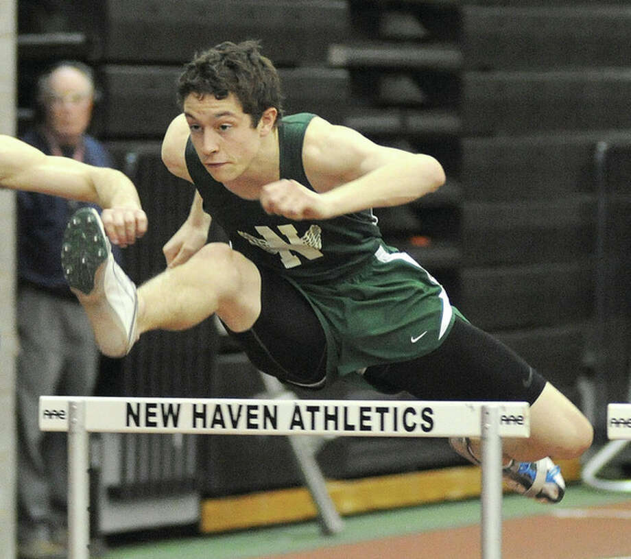 Hour photo/John Nash Norwalk High's Adam Robertino clears a hurdle en route to an easy win in his heat race at Thursday night's FCIAC championship meet in New Haven. The senior later claimed his third straight indoor hurdles title.