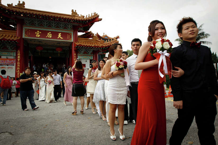 Newlywed couples walk after a photo session during a mass wedding ceremony at the Thean Hou temple in Kuala Lumpur, Malaysia, Friday, Nov. 11 , 2011. Over 200 brides and grooms attended a mass wedding ceremony at the temple, to mark the unique date of 11-11-11. (AP Photo/Vincent Thian) / AP
