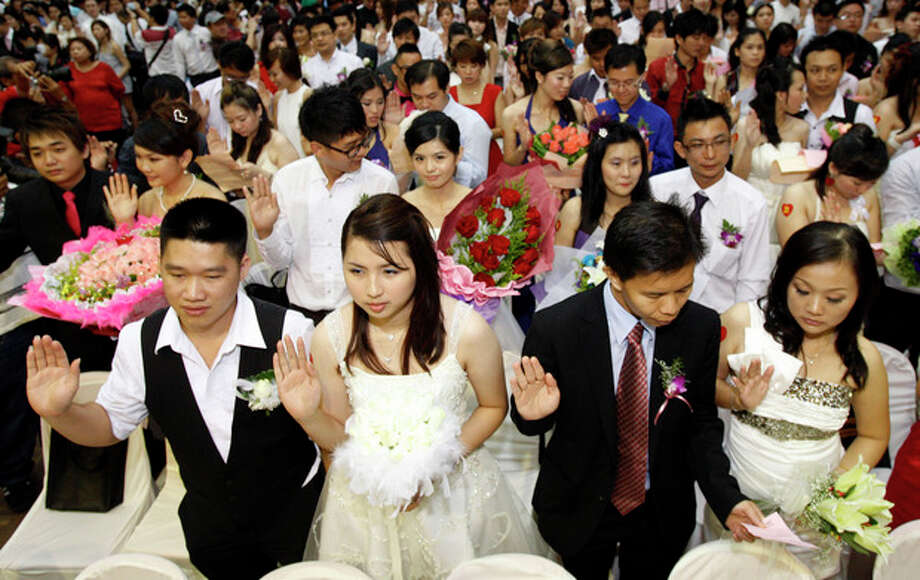 Newlywed couples swear in during a mass wedding ceremony at the Hokkien Association building in Klang, outside Kuala Lumpur, Malaysia, Friday, Nov. 11, 2011. Over 300 brides and grooms attended the ceremony to mark the unique date of 11-11-11. (AP Photo/Lai Seng Sin) / AP