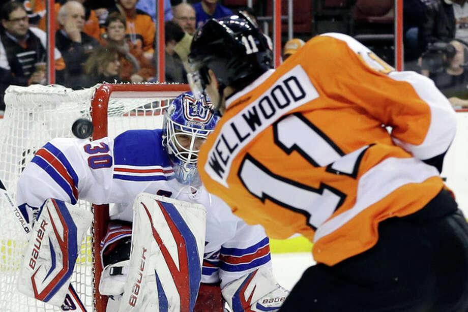 New York Rangers goalie Henrik Lundqvist, left, of Sweden, blocks a shot by Philadelphia Flyers' Eric Wellwood during the second period of an NHL hockey game, Thursday, Jan. 24, 2013, in Philadelphia. (AP Photo/Matt Slocum) / AP