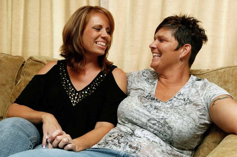 Melissa Patrick, right, and her partner Sheila Barnett share a laugh during an interview Tuesday, Nov. 8, 2011, in Port Charlotte, Fla. The couple won a dream wedding on Facebook and will be married on Nov. 11, in New York City. As Barnett and Patrick pack their warm clothes and nearly identical dresses for the ceremony , they are trying not to think about this one fact: when they get home to Florida after their whirlwind, fairy-tale weekend, their marriage won't be legal in Florida. (AP Photo/Chris O'Meara) / AP