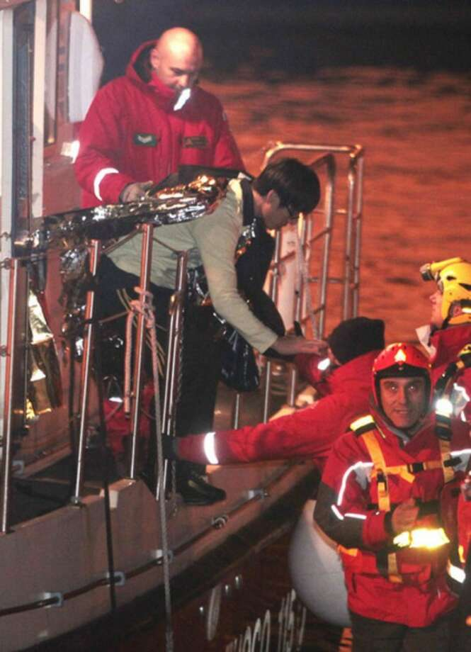 A passenger from South Korea, top left, disembarks from an Italian Firefighter boat after being rescued from the luxury cruise ship Costa Concordia which ran aground the tiny Tuscan island of Giglio, Italy, Sunday, Jan. 15, 2012. The luxury cruise ship ran aground off the coast of Tuscany, sending water pouring in through a 160-foot (50-meter) gash in the hull and forcing the evacuation of some 4,200 people from the listing vessel early Saturday, the Italian coast guard said. (AP Photo/Gregorio Borgia)