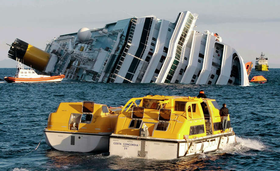 Investigators approach the luxury cruise ship Costa Concordia which leans on its starboard side after running aground in the tiny Tuscan island of Isola del Giglio, Italy, Sunday, Jan. 15, 2012. The Costa Concordia cruise ship ran aground off the coast of Tuscany, sending water pouring in through a 160-foot (50-meter) gash in the hull and forcing the evacuation of some 4,200 people from the listing vessel early Saturday, the Italian coast guard said. (AP Photo/Gregorio Borgia) / AP