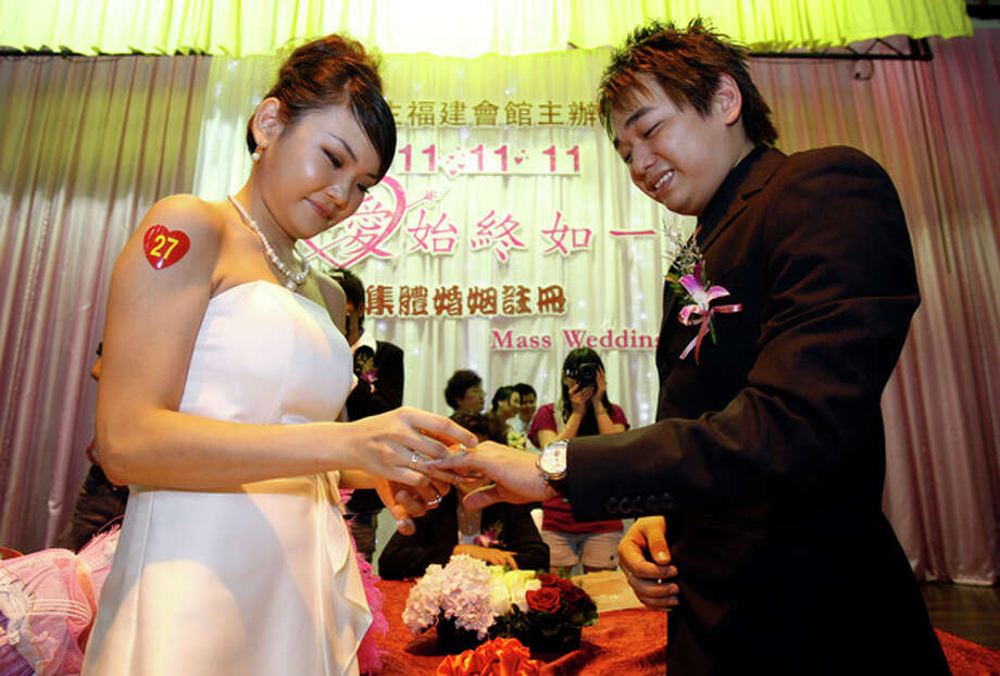Ng Woon Teng, left, 20, puts a wedding ring on Lim Chee Soon, 25, during a mass wedding ceremony at the Hokkien Association building in Klang, outside Kuala Lumpur, Malaysia, Friday, Nov. 11, 2011. Over 300 brides and grooms attended the ceremony to mark the unique date of 11-11-11. (AP Photo/Lai Seng Sin) / AP