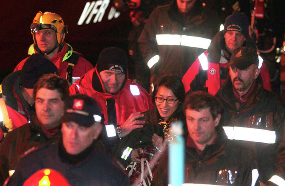 A passenger from South Korea, center, walks with Italian Firefighters after being rescued from the luxury cruise ship Costa Concordia which ran aground the tiny Tuscan island of Giglio, Italy, Sunday, Jan. 15, 2012. The luxury cruise ship ran aground off the coast of Tuscany, sending water pouring in through a 160-foot (50-meter) gash in the hull and forcing the evacuation of some 4,200 people from the listing vessel early Saturday, the Italian coast guard said. (AP Photo/Gregorio Borgia) / AP