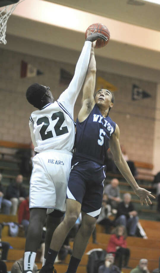 Wilton's Olondi LeGrand, right, has his shot blocked by Norwalk's Roy Kane Jr. during the second quarter of Thursday's FCIAC boys basketball game at Scarso Gym. Wilton defeated the host Bears 70-66 in overtime.