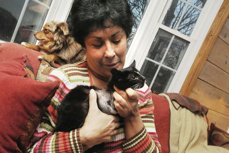 Hour photo / Matthew Vinci Nancy Corbo at her home in Norwalk. She works with Westport-based TAILS to prevent pet over popualtion.She holds Bandit, the cat who was rescued and is missing one leg, that she believes was hit by a car.